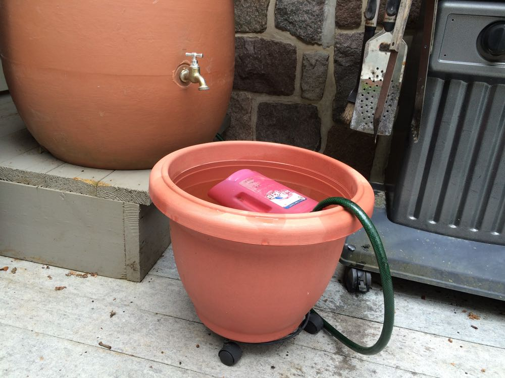 A plastic pot on wheels helps me move rain water from my rain barrel to my potted plants.