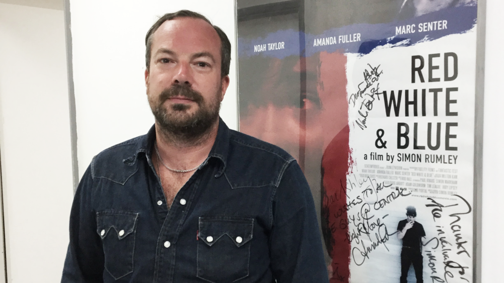 Simon Rumley, director of Fashionista, in front of his signed poster for Red White & Blue at Central Film School