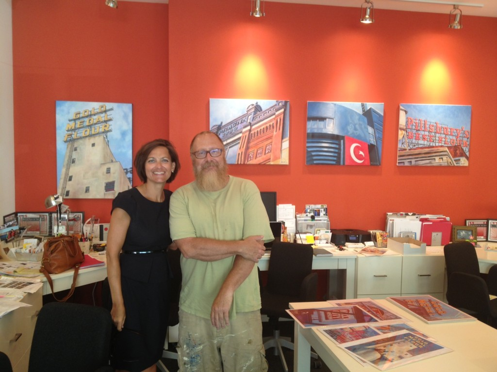Artist Mike Welton & Cindy Froid in front of the Gold Medal Flour, Pracna, Guthrie Theater, and Pillsbury paintings.