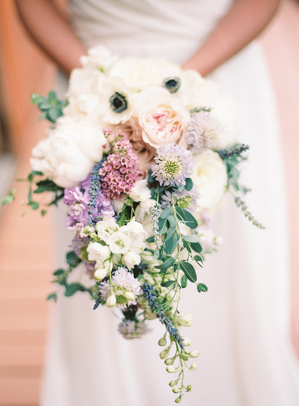Cascading soft watercolor tone garden-style bouquet inspired with a bit of lavender. This is one of my favorite photos with the soft lighting and detail shot of the special florals in Jessica's bouquet.   Cottrell Photography  |  Wolf Mountain Vineyards