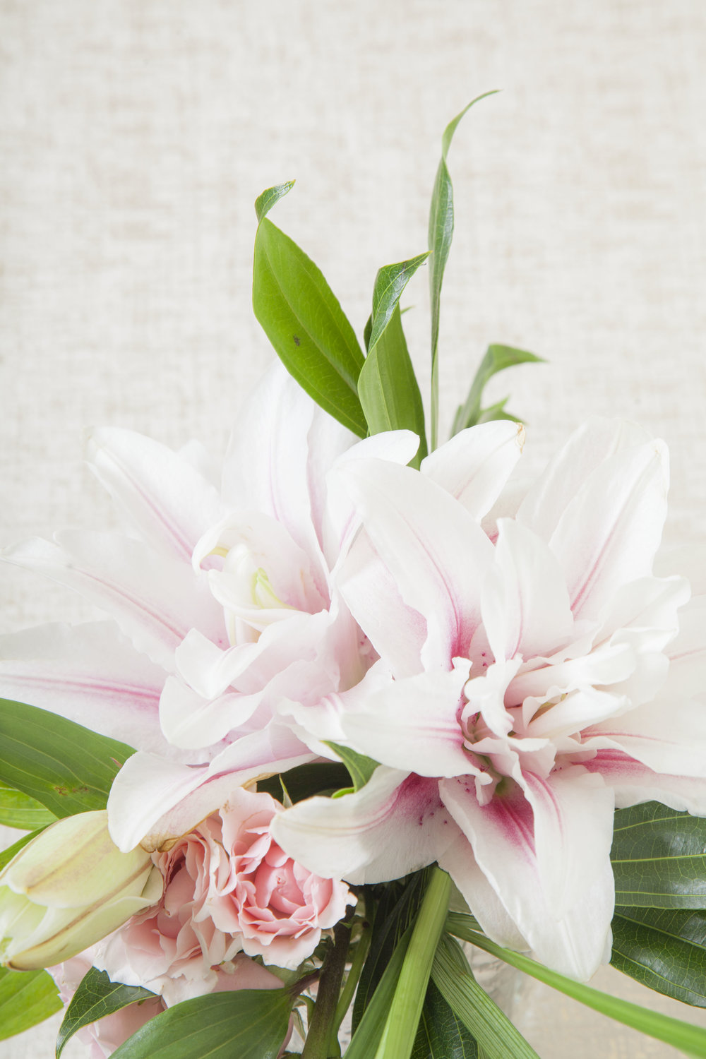 Pink lilies with pink majolica spray roses and more.