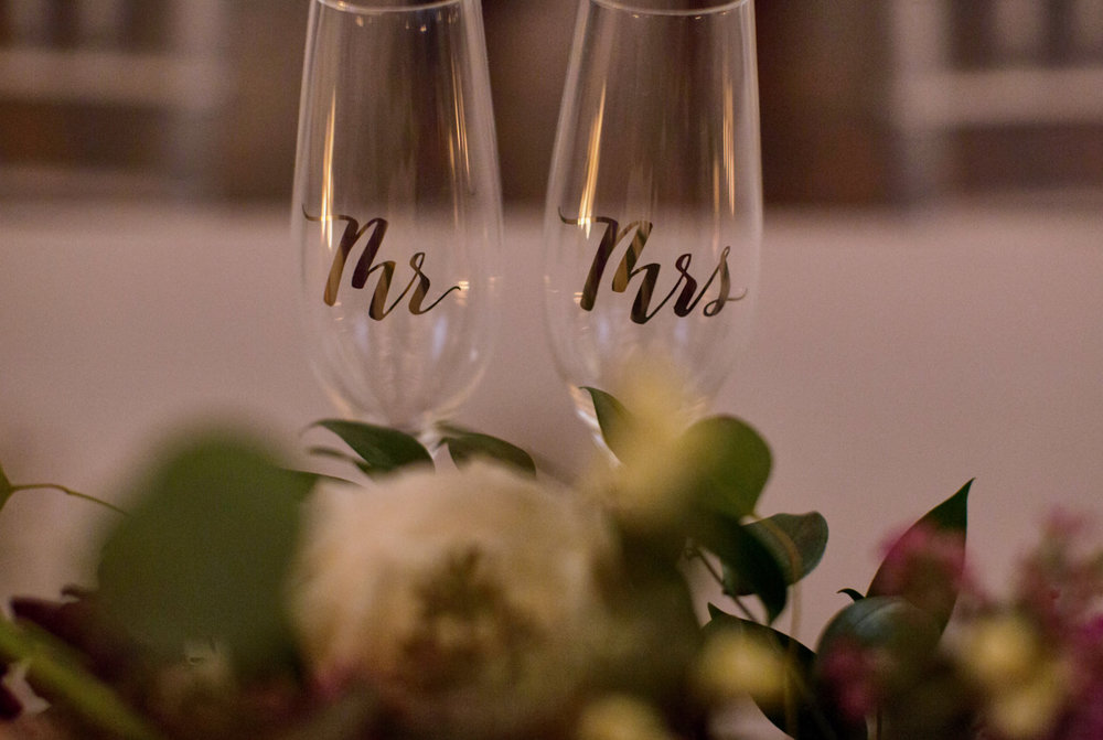 Mr. and Mrs. Champagne flutes by sweetheart table decor  Photography by Joya Chapman from  JGCaptured.com .