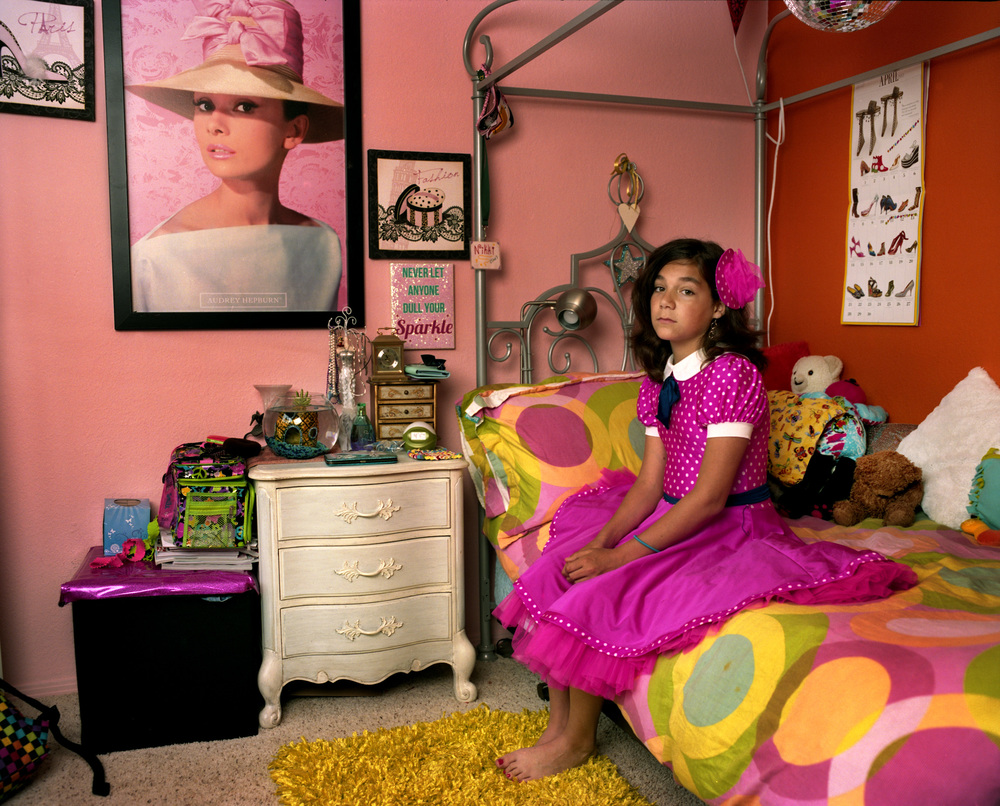 "Nikki in her bedroom, California, 2013   Nikki was born Niko. A biological boy at birth, she began at the age of 10 the complicated transition to becoming girl. With the utmost support of her family and friends, two years later, she is living happily as the person she always knew herself to be — singing, acting and dancing, often draped in pink. ""I hated living as a boy,"" Nikki says. ""I love this life so much more."""