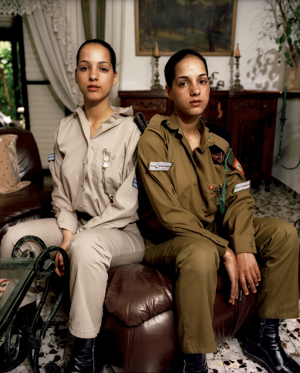 Tal and Moran  Tel Aviv, May 2002  We're Tal and Moran, twin sisters, both in the army. In this picture, we had just arrived at home for our weekend off from the army and were getting ready for Shabbat dinner, a time when our entire extended family gets together at our house. Our father built this community, so all our relatives live close by. We look forward to these Friday night gatherings with the cousins all week. We try to come home every other Friday. Going to the army at the age of eighteen puts a huge responsibility on our shoulders. It is a big honor to have the opportunity to give back to our country that we love very much, but it also gives us a whole new perspective on life. We have to become adults in a very short amount of time, but learning this kind of commitment feels good. These aren't such good days for Israel. The future is uncertain.