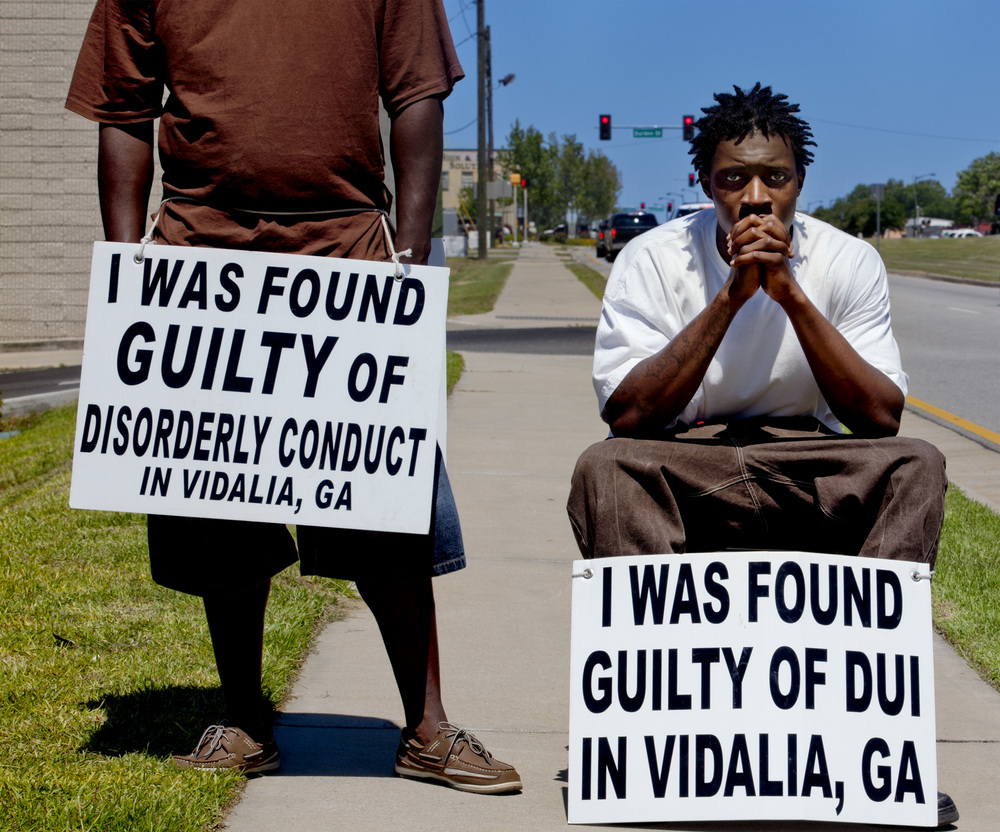 Public shaming, Vidalia, Georgia, 2013   I was [caught] urinating outside of a nightclub. I could either walk with this sign or go to jail. It's humiliating, but better than being behind bars. We have to walk up and down the street for eight hours every day this week.  —Lourinza (in brown shirt)