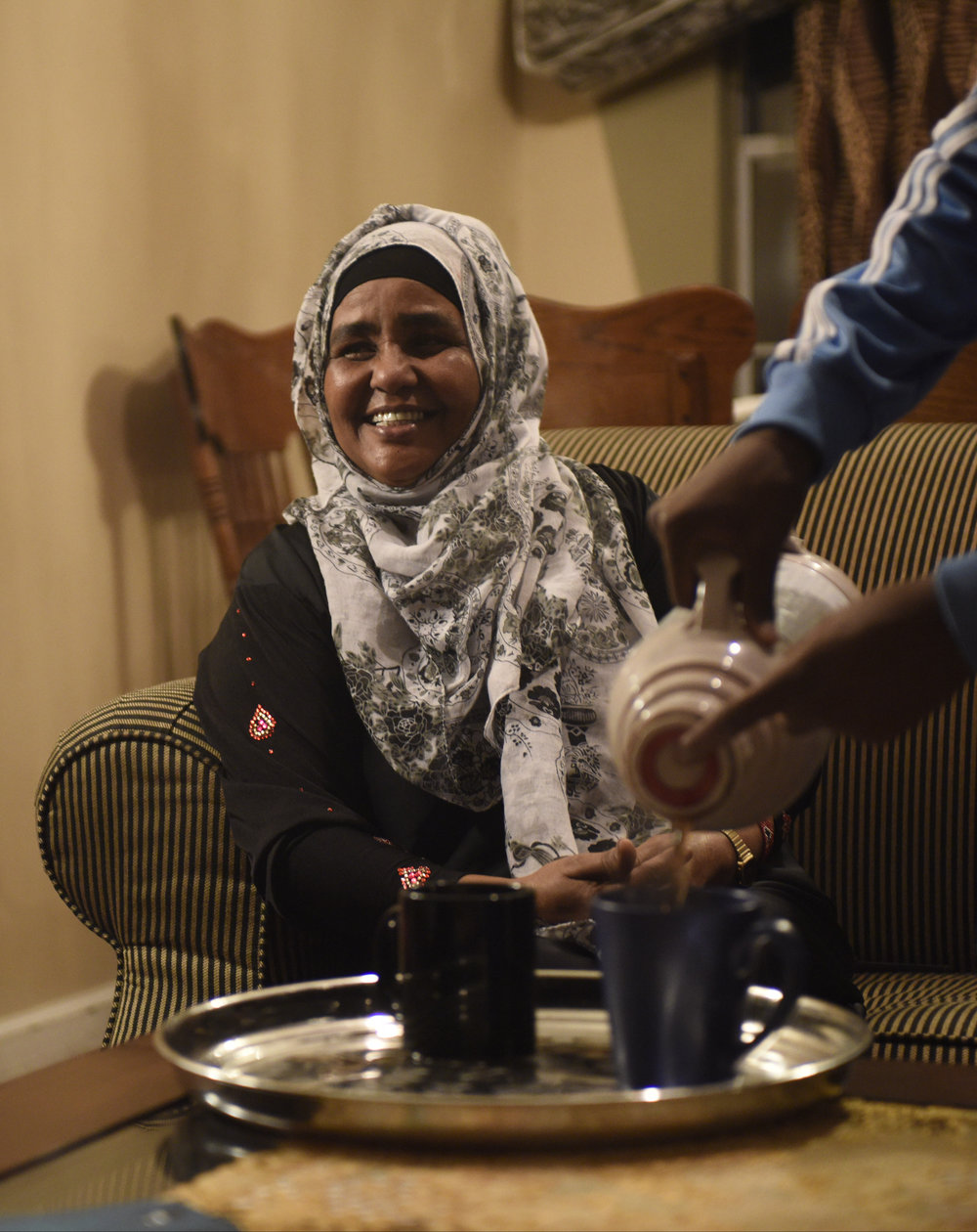 "Kaho Barre, mother of Yasin Abdirahman, smiles at her family while sitting in their living room after arriving back from the airport on Tuesday, April 18, 2017. Barre said that from the day she first arrived in Columbia until the night her son arrived, she was prepared to go to the airport and get him. ""I was not happy until I saw his face,"" Barre said."