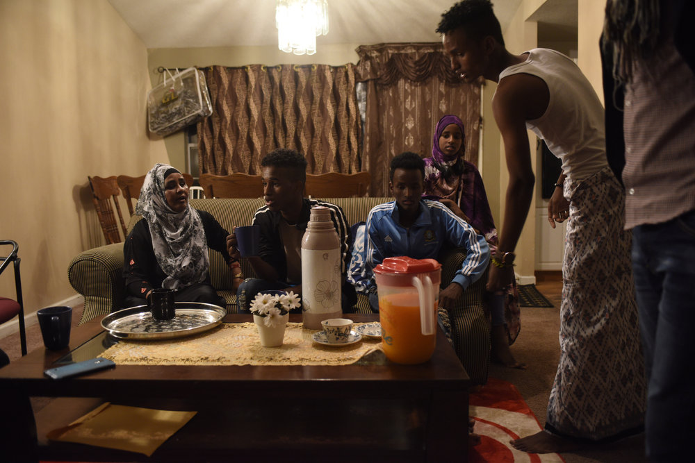 "The Abdirahman family gather in their living room to drink tea and sign paperwork from their case worker after returning from the airport on Tuesday, April 18, 2017. ""We are all happy tonight. We are not sleeping tonight. The family [is] gathered together again,"" said Barre."
