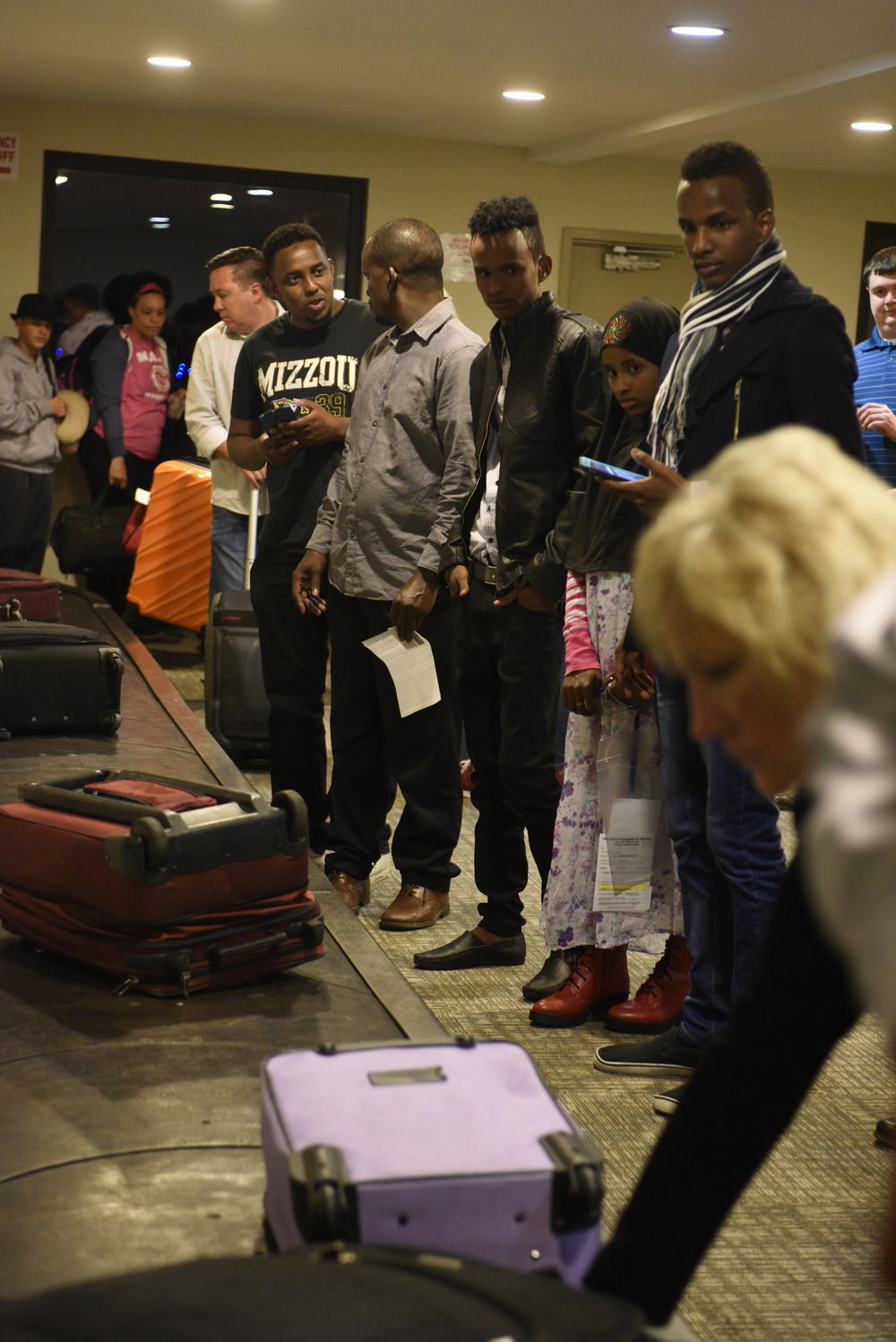 "The Abdirahman family looks for Yasin's luggage at the baggage claim at the Columbia Regional Airport after months of separation on Tuesday, April 18, 2017.  I was by myself. Yasin spent two months alone in Ethiopia. ""I was going to school in the morning. And I was sleeping in the afternoon. All the night I would stay in the house by myself. It was lonely,"" Yasin said."
