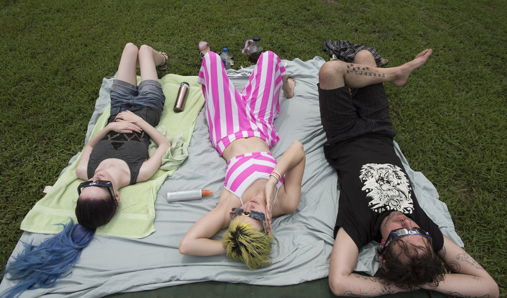 Rachel Hermes, Hollie Hermes and Johnny Carcaz lay in the meadow and stare at the sky to view the eclipse. The group came with the burners and have come from Kansas City and Manhattan, Kansas.