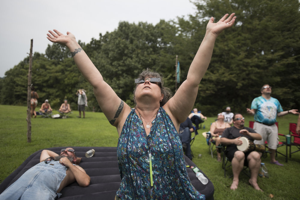 Phoennix Norton raises her arms to the sky and sings as the sun reaches closer to the point of totality