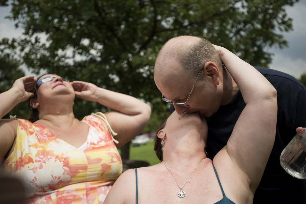 From left, Lisa Bruce looks at the eclipse as Kendal Gravitt and Bryant Biek kiss under the sun after witnessing totality. All of them have been involved with Oak Spirit Sanctuary since 1991. Gavitt and Biek met and were married at Oak Spirit over 20 years ago.