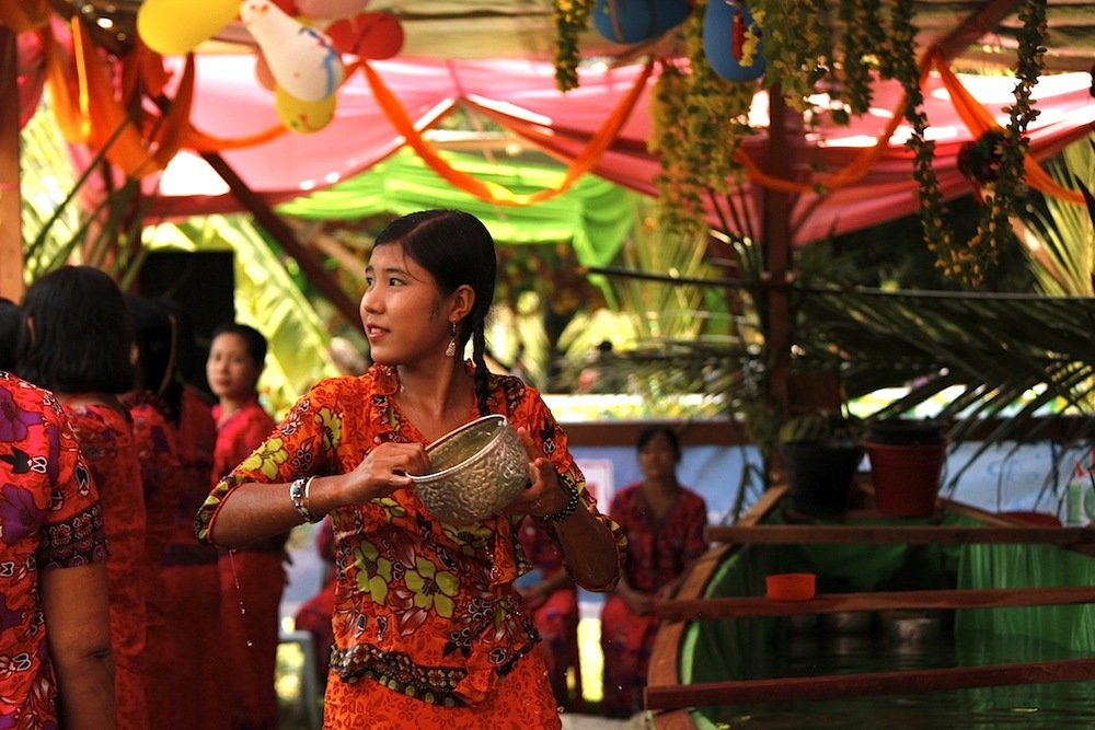 A girl pours water on Yangon partygoers during the Water Festival