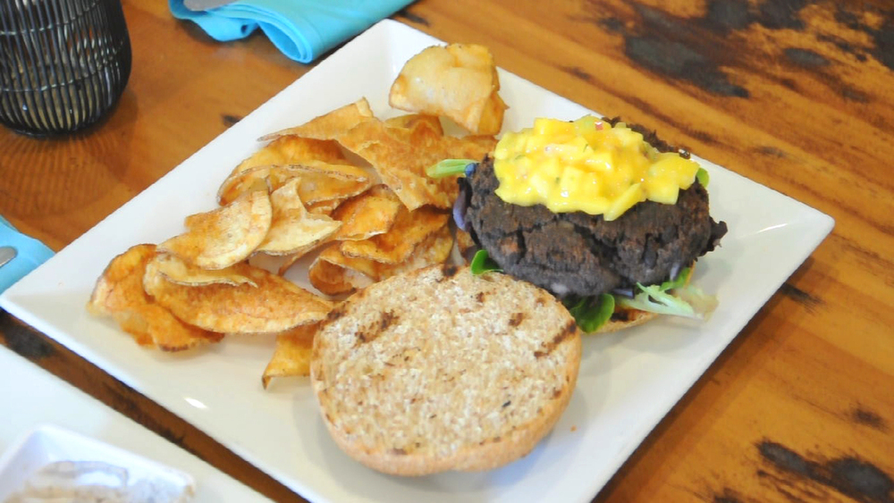 Vegan black bean burger with mixed greens, mango salsa, and a side of chips