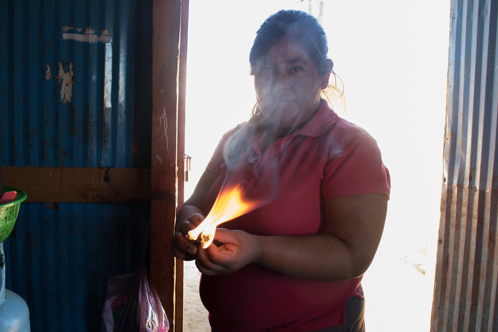 Herminia Vargas, 32, burns wood in preparation to light her stove to cook dinner  in Zaachila, Mexico on Thursday, Jan. 12, 2017.