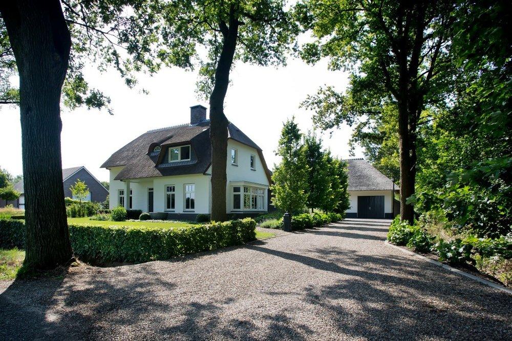 Siebers-Tuinprojecten-Tuin-Hovenier-Inrit-Grind-Nidagravel-landelijke-wit-huis-rieten-kap-dak-stijl.jpg