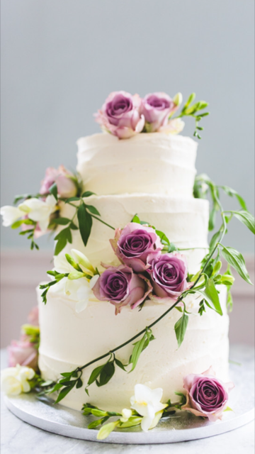 A simple rustic buttercream cake dressed with fresh flowers by Emma Page Buttercream Cakes London. Garlands of foliage create movement between the tiers