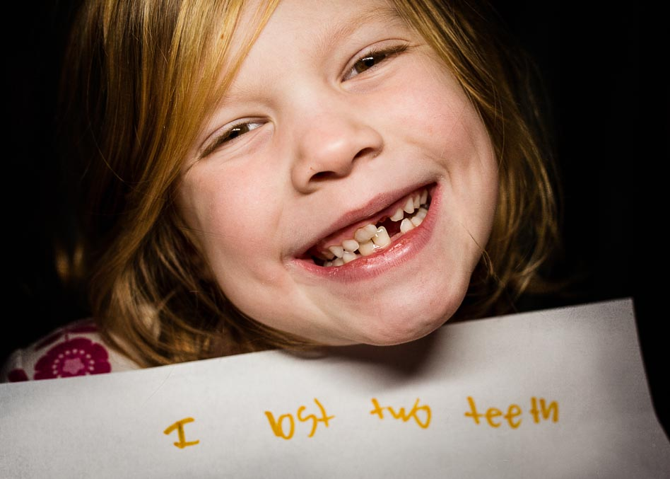 Image of smiling girl holding note to tooth fairy