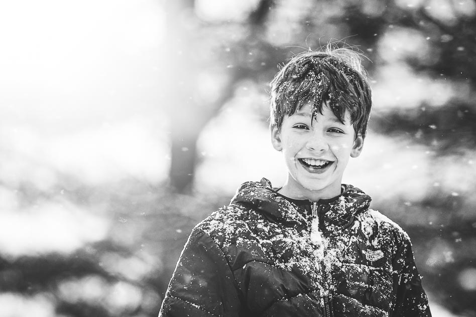 Black and white image of boy playing in snow