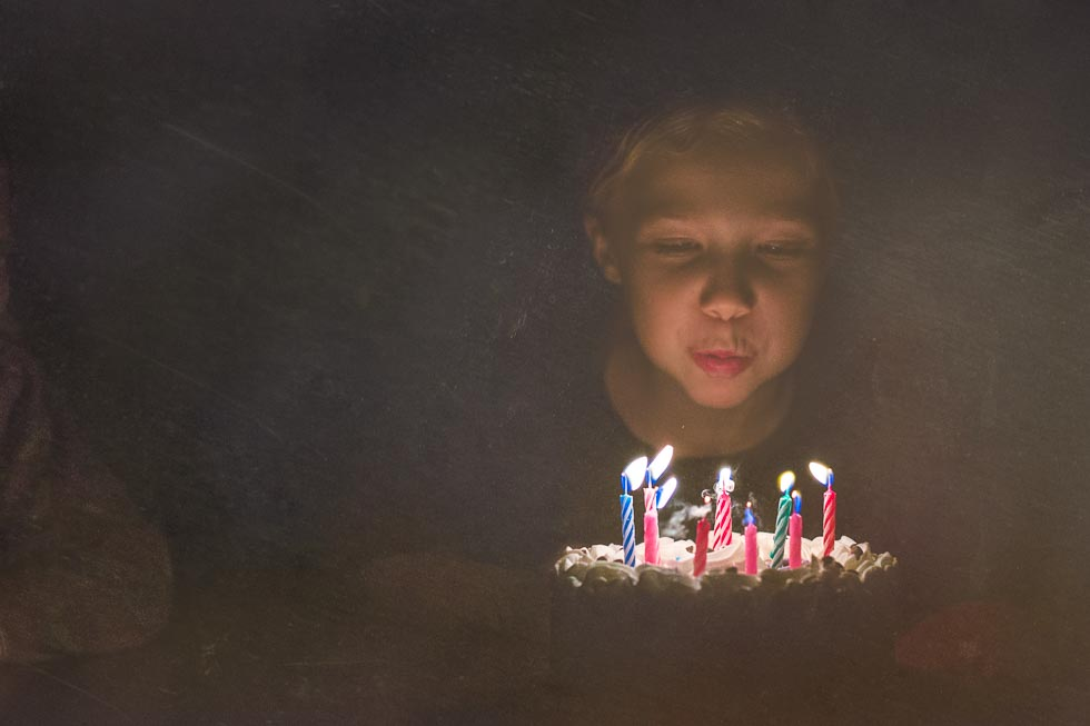artistic image of young girl blowing out multicolored candles on her birthday cake in the dark