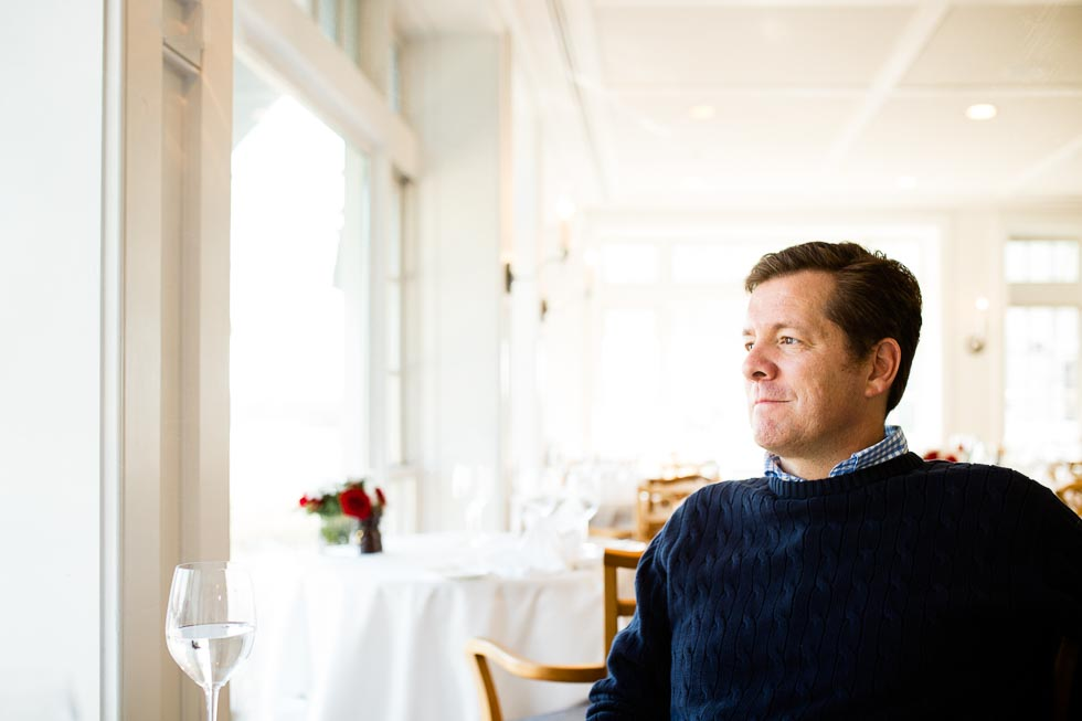 Man relaxing at a table by a window in a gorgeous white table cloth restaurant Starz at the Inn at Perry Cabin in St. Michaels,, MD