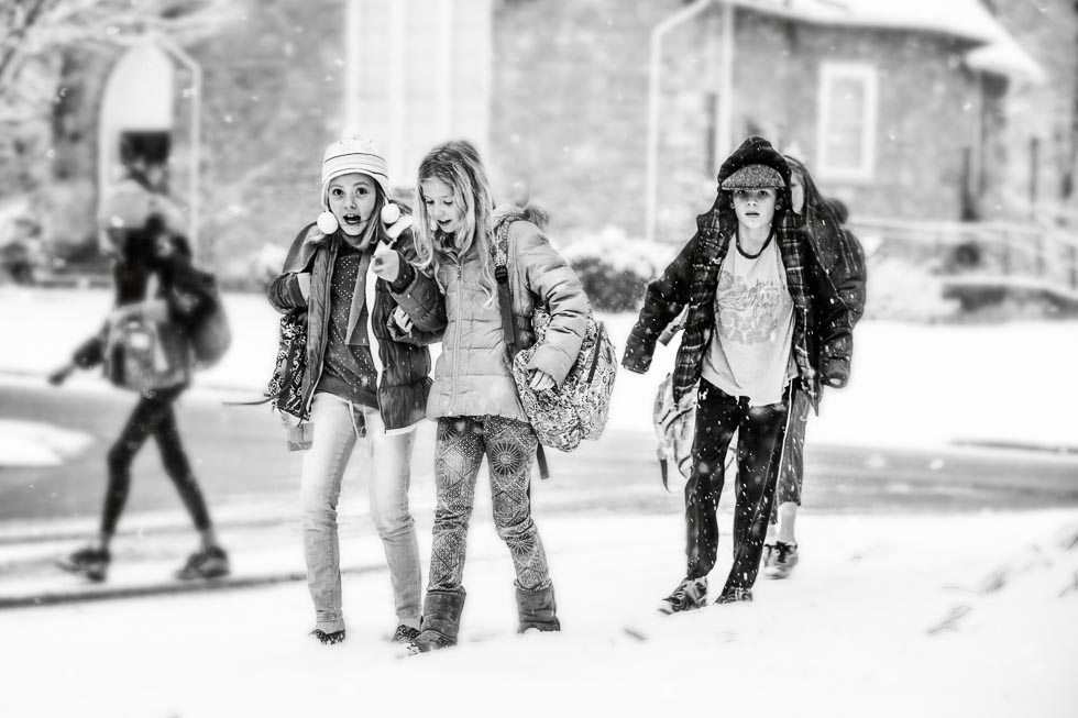 Black and white image of kids walking home from school in the snow.
