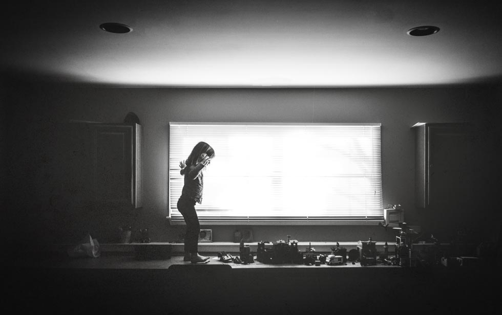 Black and white image of small girl standing on a counter of legos in front of a long, wide window.