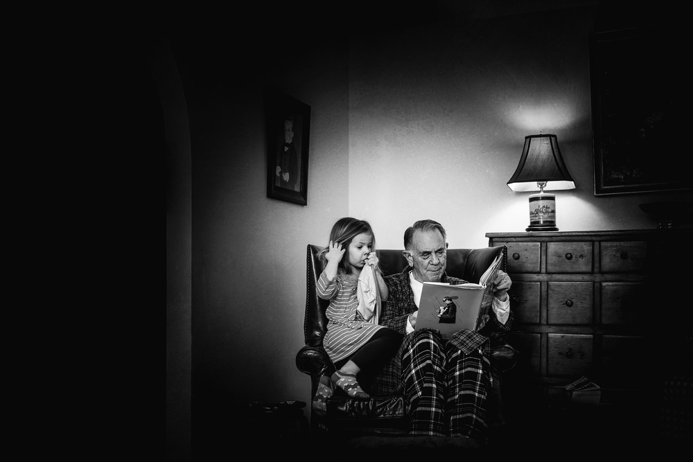 Little girl reading a book with her grandfather.