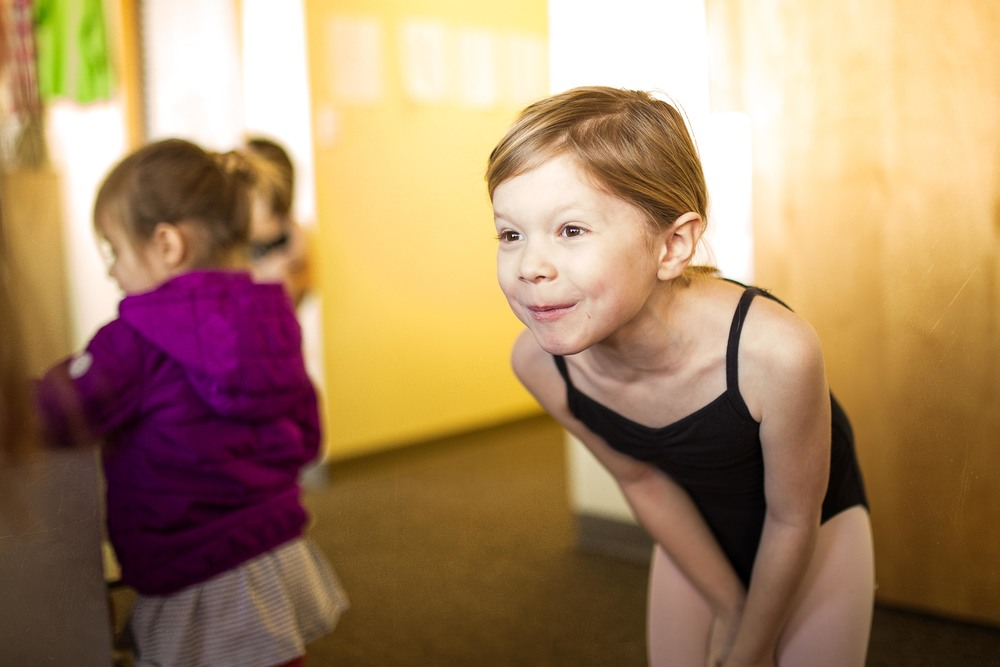 Little girl looking happy in a black leotard after her ballet class.