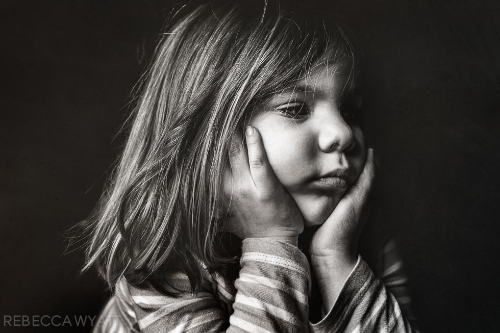 Adorable black and white photograph of girl with her hands to her chubby cheeks.