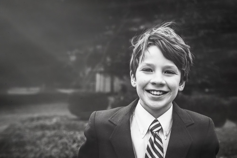 Handsome black and white photograph of eleven year old boy in a suit smiling on a windy day.