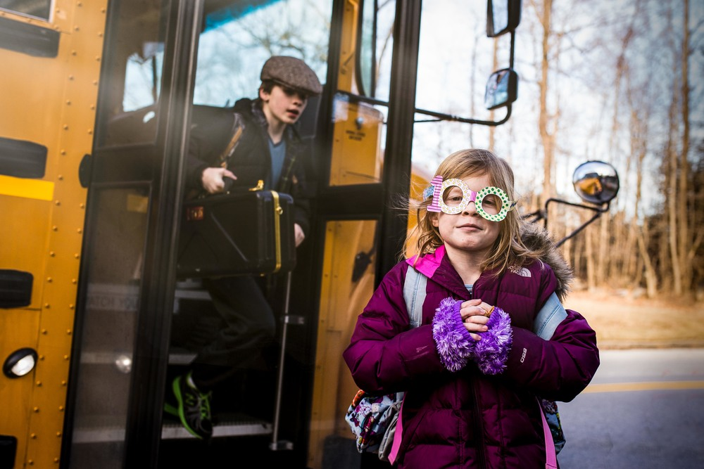 Color photograph of two children exiting school bus with the girl wearing paper glasses in the shape of 100.
