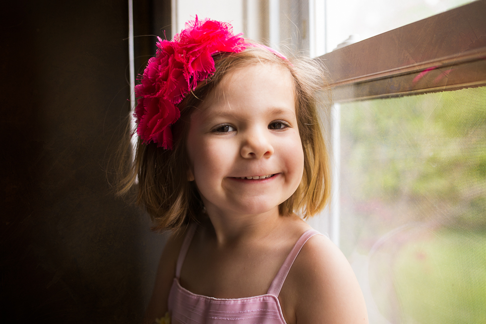 window lit portrait of a young girl smiling with a pink headband