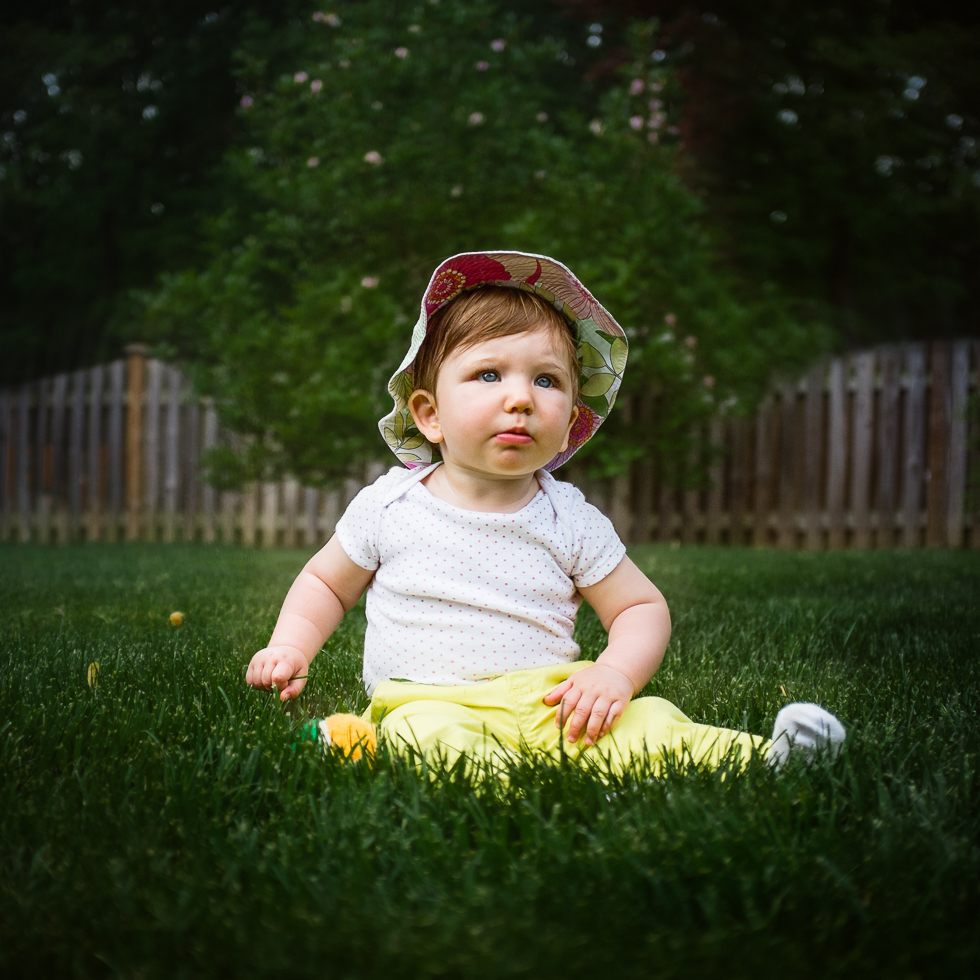 Gorgeous baby sitting in the grass on Mother's Day