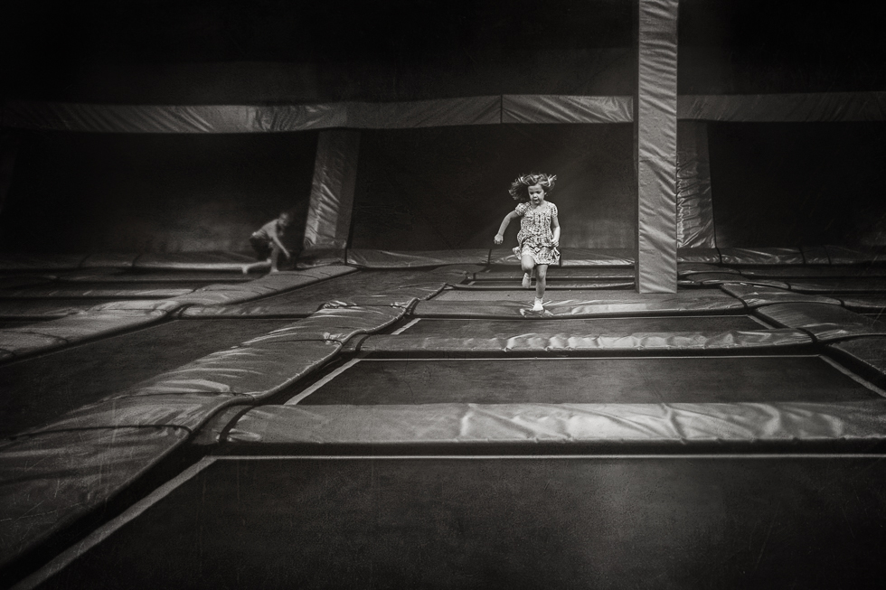 Young girl running on trampolines at trampoline park in black and white photography.