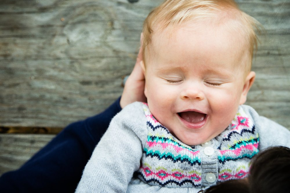 baby girl laughing with in her dad's arms on a picnic table.