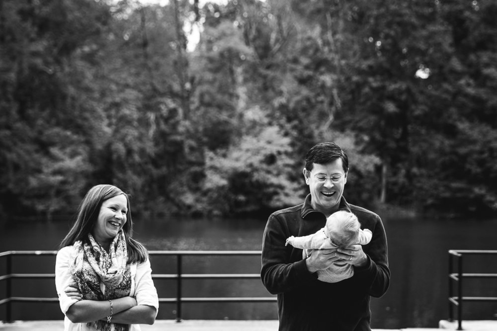 candid black and white photo of mom laughing while dad is smiling and playing with baby girl.