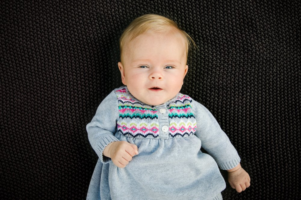 portrait of baby girl with blue eyes and blonde hair in gray dress.