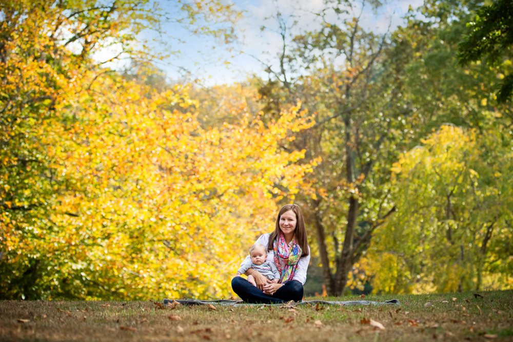 portrait of mom sitting cross legged on a blanket in a park wit beautiful baby girl sitting in her lap.