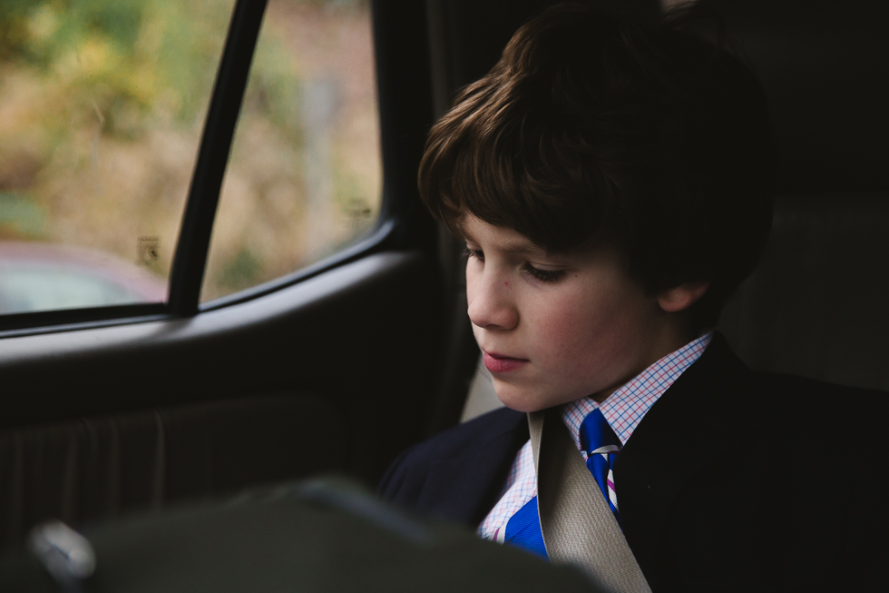middle school boy in jacket and tie reading in back seat of the car