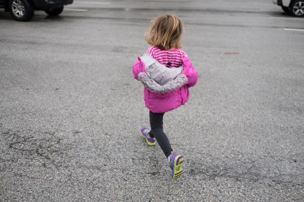child in purple jacket running across parking lot in the rain