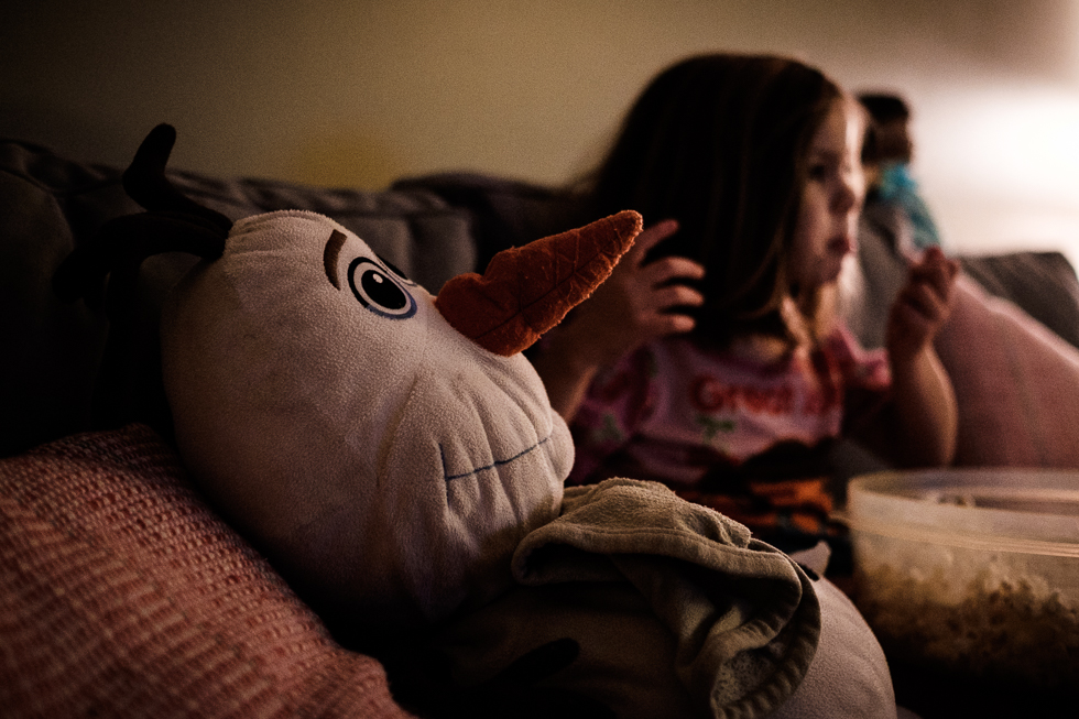Young girl eating popcorn watching a movie next to her large Olaf stuffed animal.