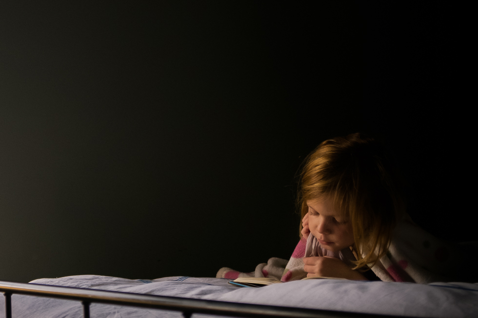 Second Grade girl reading a book in her mother's bed . Photo taken with Fuji x100t