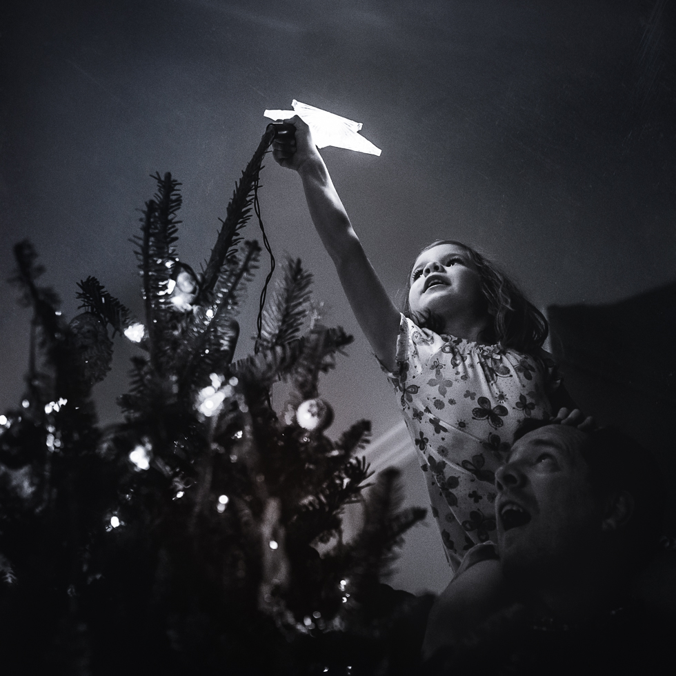 black and white photo of girl on her father's shoulders putting star on top of Christmas tree