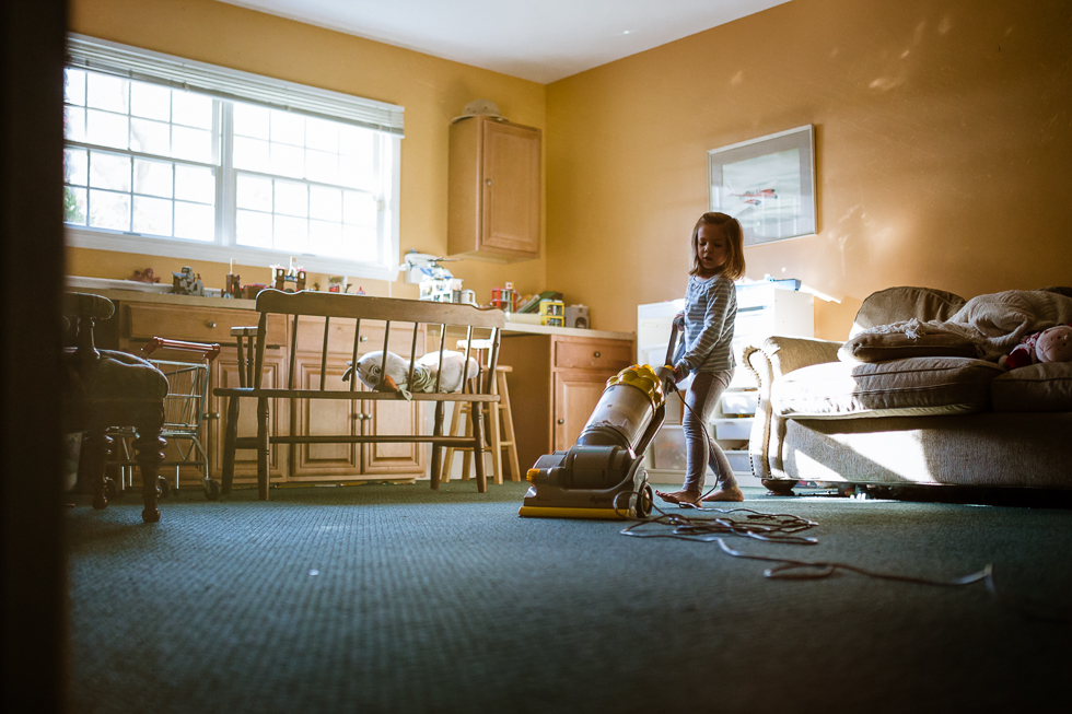 color photo of little girl vacuuming playroom