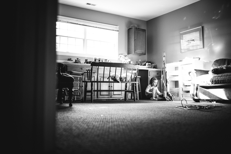 black and white photo of girl in basement playroom wrapping cord on vacuum cleaner.
