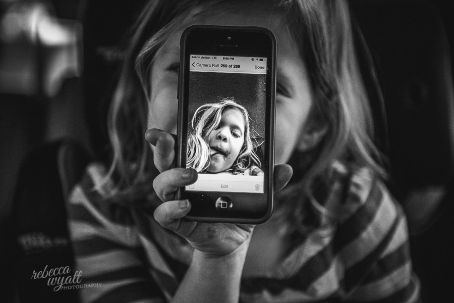 black and white girl holding iPhone with her image