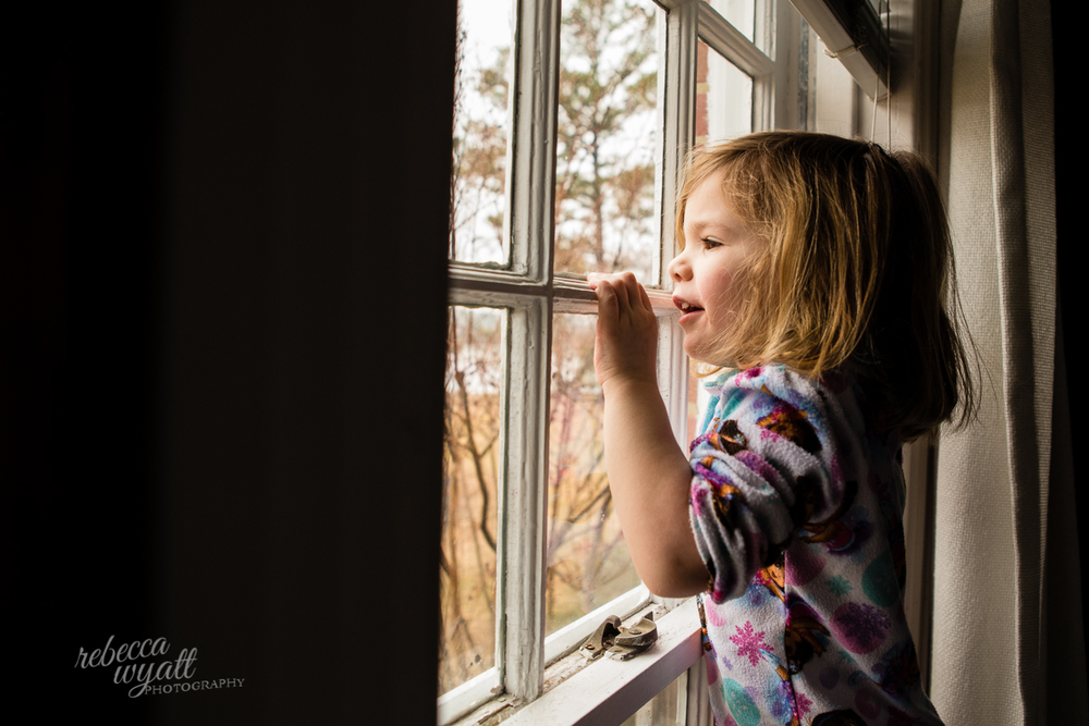 Little girl on Farm looking out window