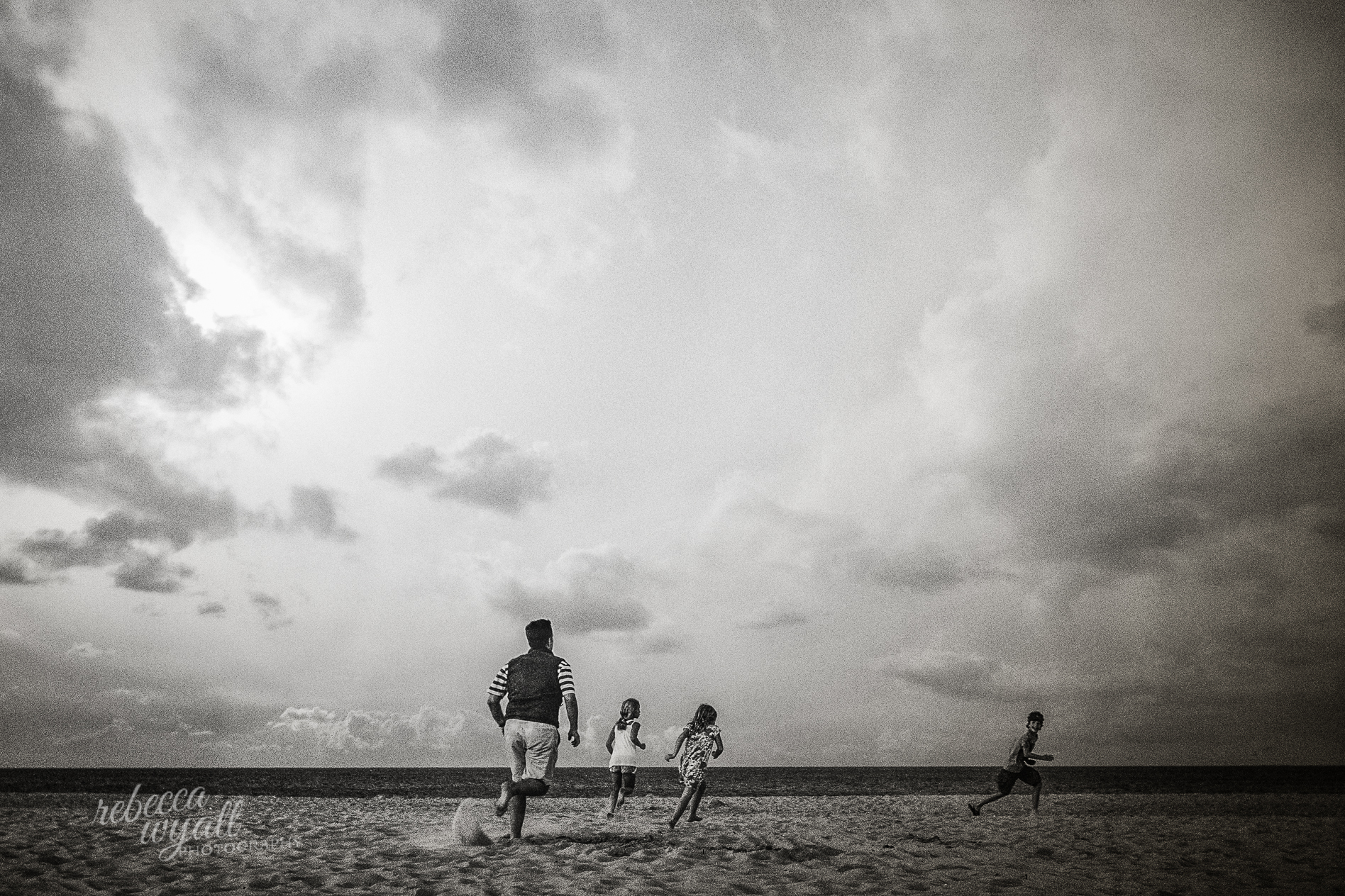 Dad & Kids Running on Beach in Black and White