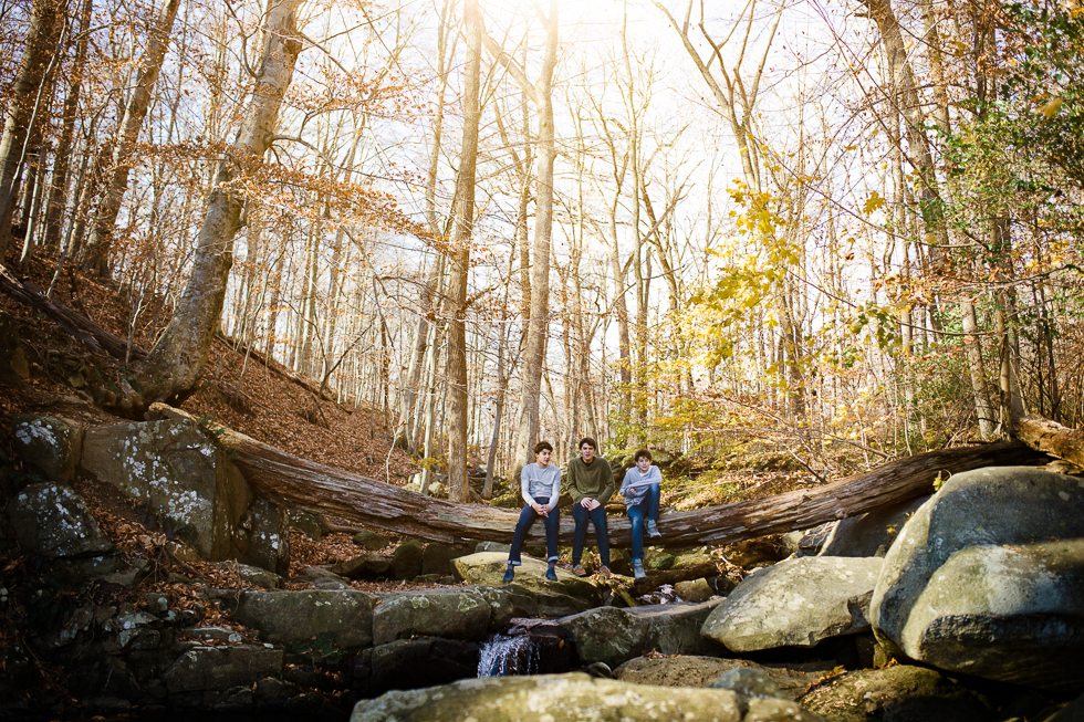 Copy of Golden light in photograph of three brothers sitting on log over a stream in the woods.