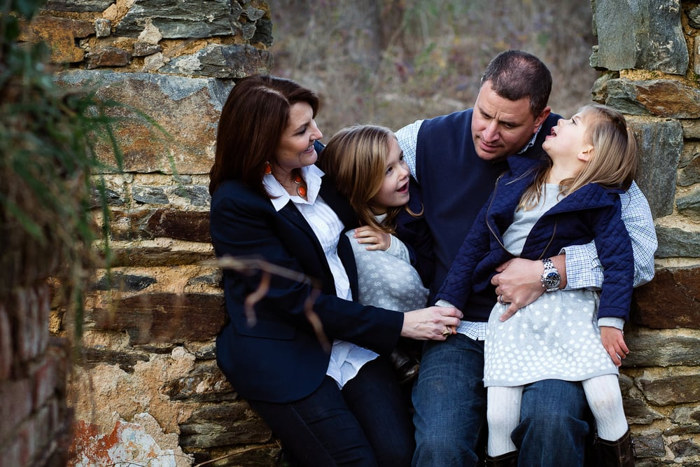 attractive family with two daughters laughing and smiling in family portrait.